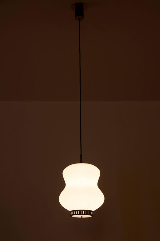 """Three brushed satin glass and brass pendants by Stilnovo. Designed in Italy, circa 1950s. Original canopies with custom brass plates. Wired for US 3.75"""" junction boxes. Each pendant takes one E26 75w maximum bulb. Overall drop can be adjusted."""