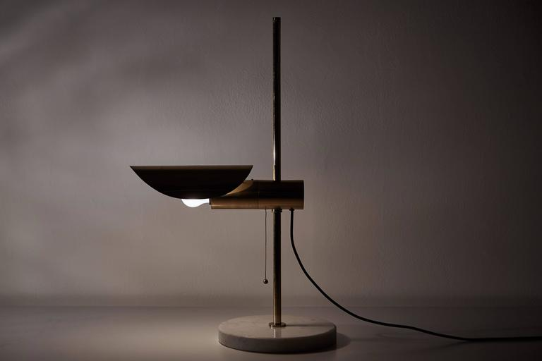1950s brass table lamp with marble base and pivoting shade. Designed in Italy, circa 1950s. Brass shade pivots left to right. Original cord. Takes one E14 75w maximum bulb.