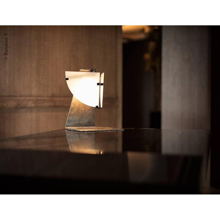 Quart de Rond table lamp originally designed  by Pierre Chareau in France, 1922. Current production by Galerie MCDE. Composed of two panels of alabaster in quarter-wedges adjustable. Base in forged blackened metal and darkened wrought iron and