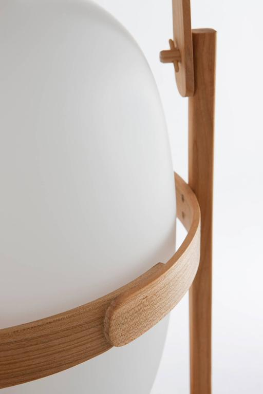 Cesta Table Lamp by Miguel Mila for Santa & Cole. Originally designed in 1962 in Spain. This handcrafted lamp consists of a subtle cherry wood structure that holds an opal-shaped glass shade. Cesta is an excellent object and lamp, perfect for