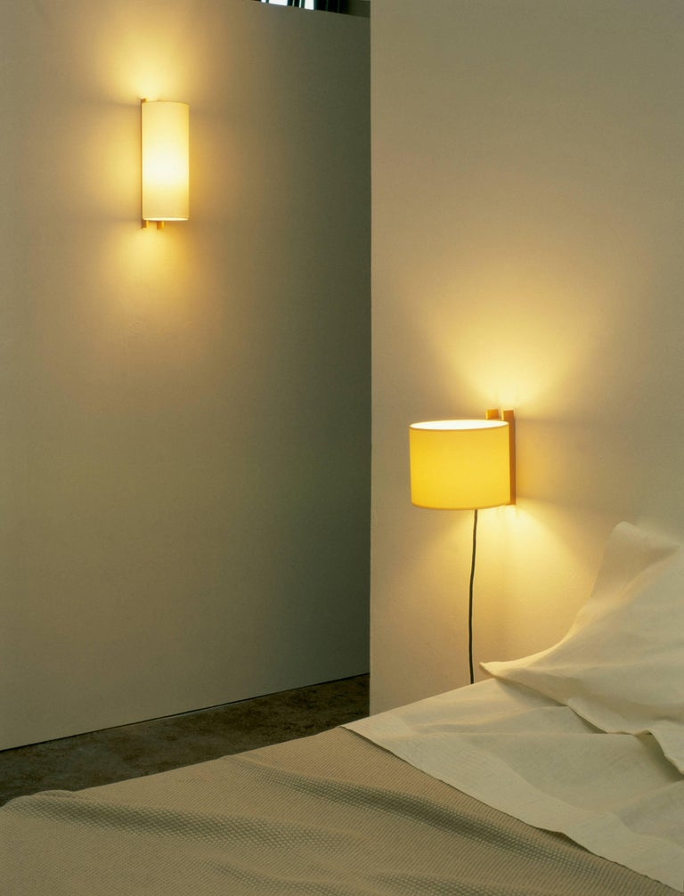 TMM Largo Wall Light by Miguel Mila for Santa & Cole. Originally designed in Spain in 1964. The TMM collection of short and long wall lamps comprises a simple beech channel into which the white or beige parchment shade is partially inserted. The