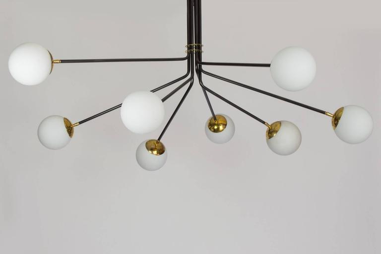This chandelier combines brass, opaline glass and black enamel to create a wonderful Mid-Century inspired chandelier. The eight lights provide a lot of light, it is a large-scale chandelier which will work nicely in an entry or a dining room. The