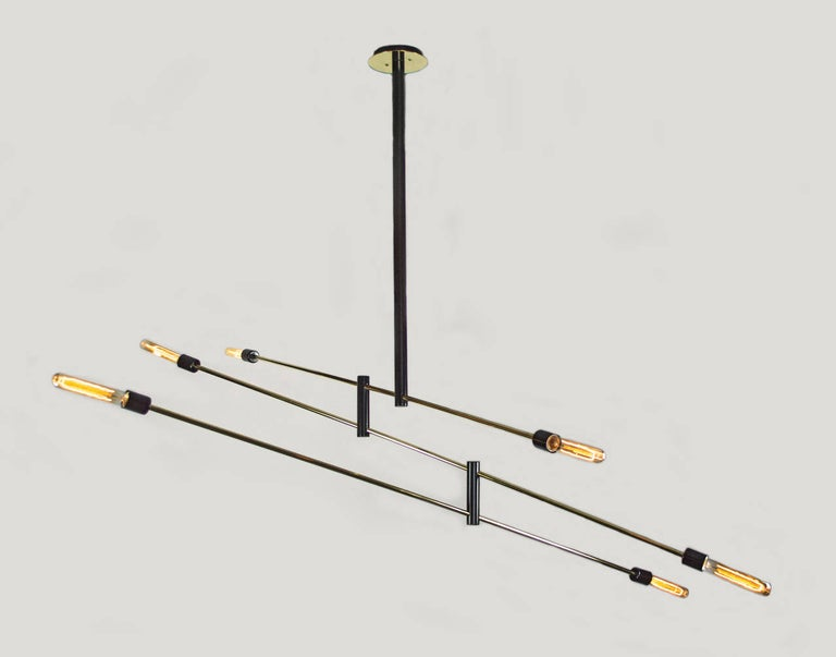 Simplicity at its finest. This distinctive chandelier is a dynamic presence in any room. The light is articulated which allows it to be moved like a mobile to create various Silhouettes. The black enameled frame with its brass tubing and canopy