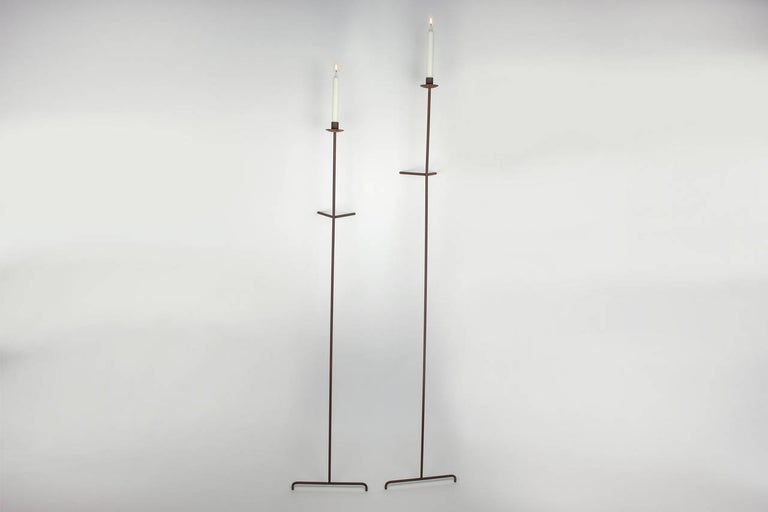 Two versatile candle holders. They lean against the wall and can be place almost everywhere to provide lighting. These candle holders are steel with a gun metal patina. They each use one taper candle each.