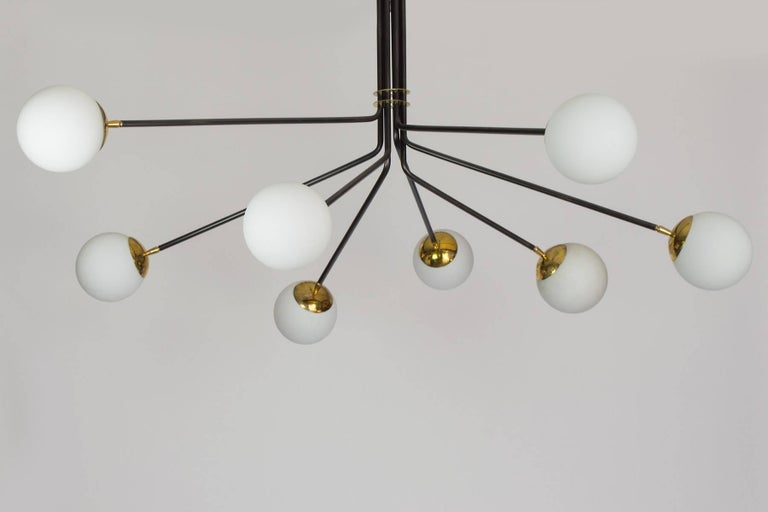 This chandelier combines brass, opaline glass and black enamel to create a wonderful midcentury inspired chandelier. The eight lights provide a lot of light, it is a large-scale chandelier which will work nicely in an entry or a dining room. The