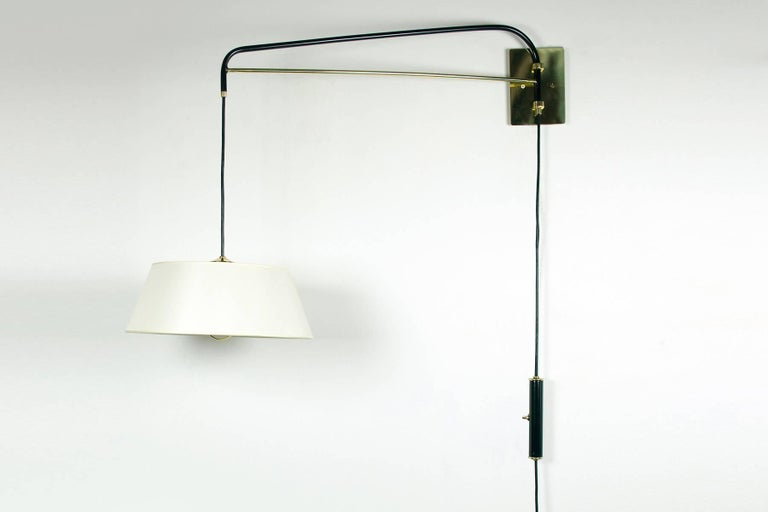 These graceful wall sconces are handcrafted by Bourgeois Boheme Atelier. They are made with a black enamel finish and polished brass. An elegant linen shade diffuses a soft light. These fixture are adjustable, the switched counter weight system
