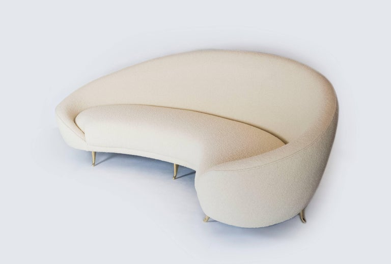 This chic sofa, reminiscent of the 1960s, has elegant lines with gracious curves. The brass feet add to its sophistication with their delicate design. It will surely be the focal point of any room. The kidney shape of the sofa provides plenty of