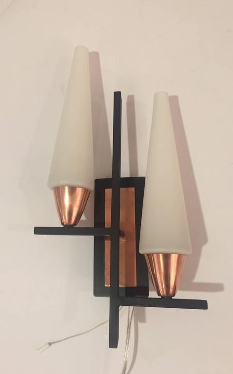 Two geometrically inspired wall sconces with copper accents and opaline glass diffusers. Each light has two European based sockets (adapters to American bulbs are provided). They also have a switch wire on each wall support. The back plates have
