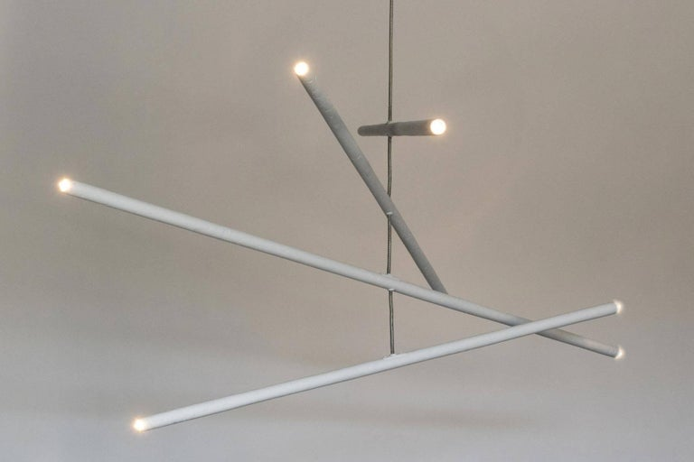 This intriguing chandelier floats in the air like a mobile. The hand finished plaster rods are fitted with voltage halogen sockets and are suspended from a stainless steel wire. The eight lights provide a perfect ambience and light the room with a