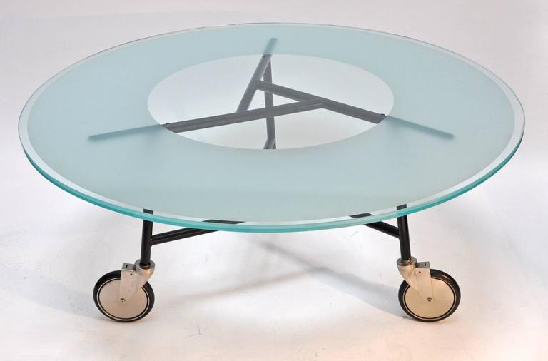 Rare glass top table designed by Ward Bennett. The 60 inch diameter sandblasted glass tops sits upon a painted tubular frame mounted on wheels.