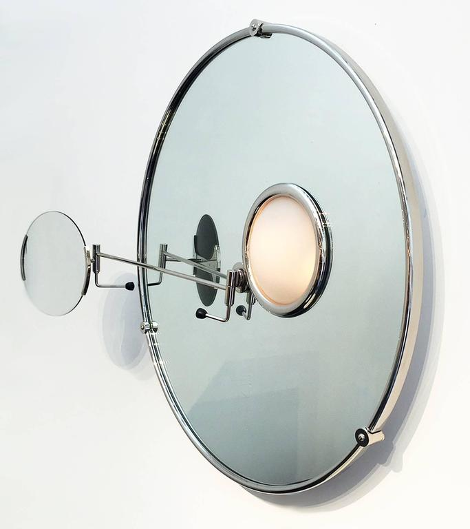 Eileen Gray created this satellite mirror for her home in the South of France, 1927. This is a current production made of nickel plated brass and glass. Illuminated portion has a sand blasted glass cover. Features an adjustable magnifying mirror