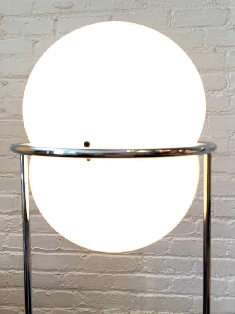 1970s modern floor lamp. features white plastic shade, polished chrome steel frame, and a three way socket.
