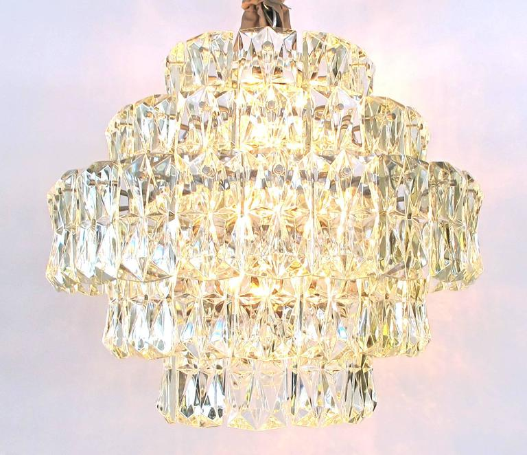 A striking German 1960s Kinkeldey Lighting five-tier chandelier with polished chrome frame and molded crystals; this shimmering Mid-Century Modern five-tier chandelier with its rectangular faceted crystals by Kinkeldey Lighting, Bad Pyrmont, Germany.