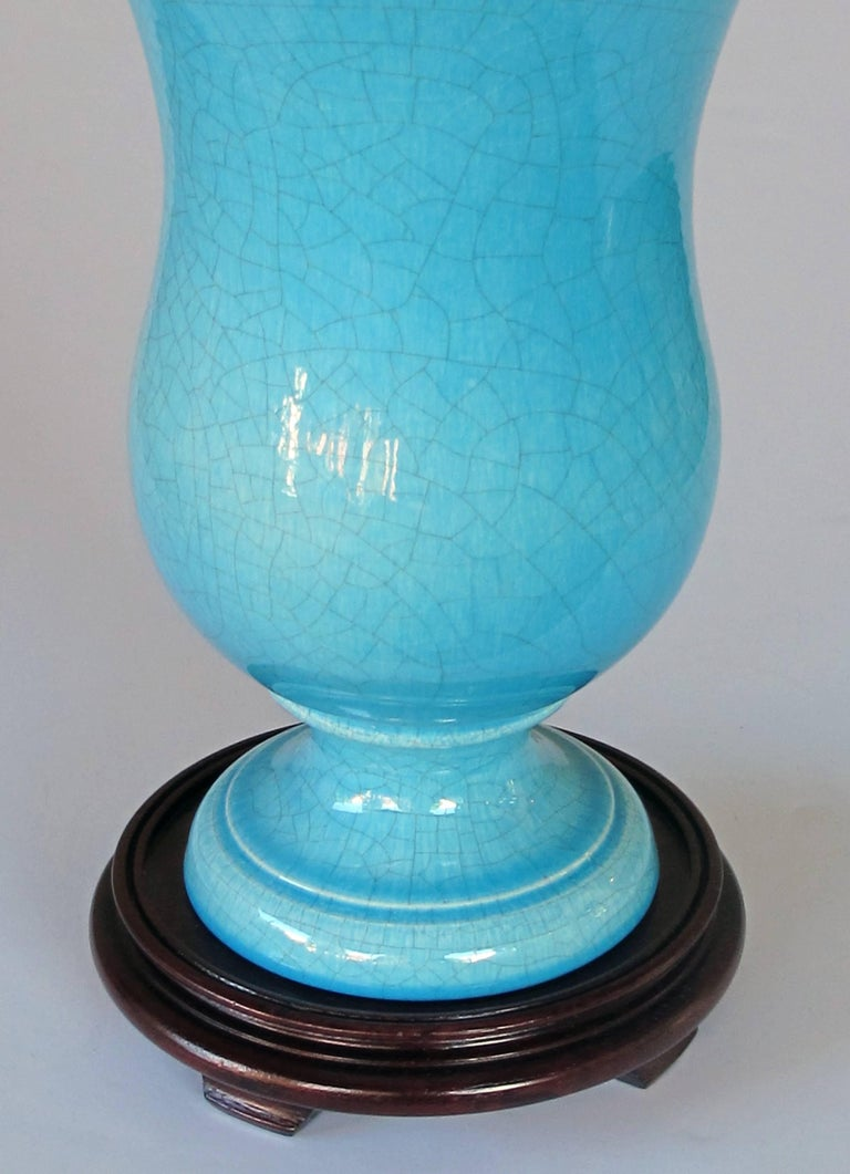 A striking and robust pair of French Art Deco turquoise crackle-glazed urns now mounted as lamps; each large-scaled urn with sweeping flared neck tapering to a flared foot; now drilled with later wooden mounts.