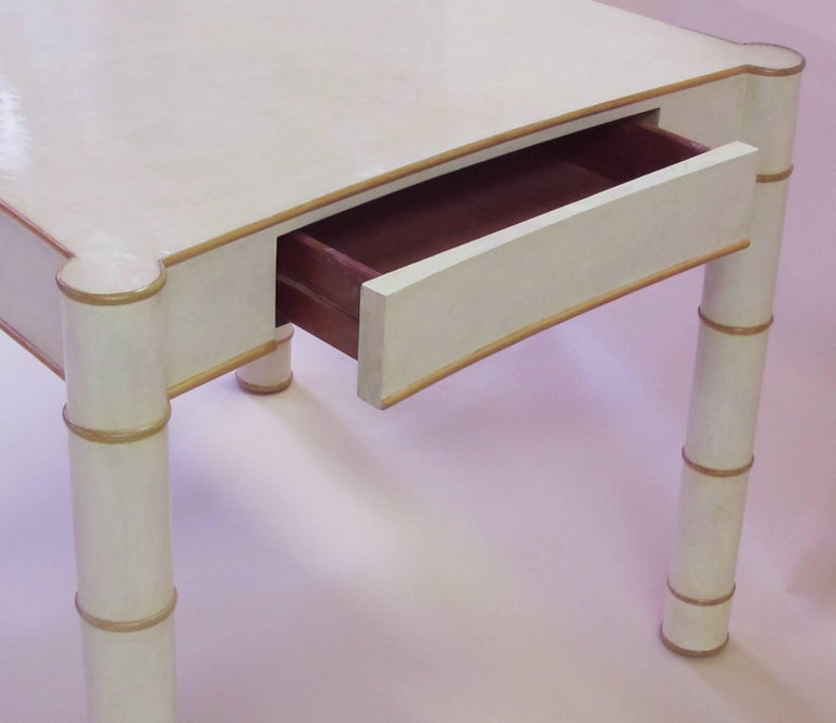 A stylish American 1970s parchment-veneered faux bamboo game table; the square top with incurved and exaggerated corners; the apron fitted with a single drawer, all raised on bold faux bamboo supports.