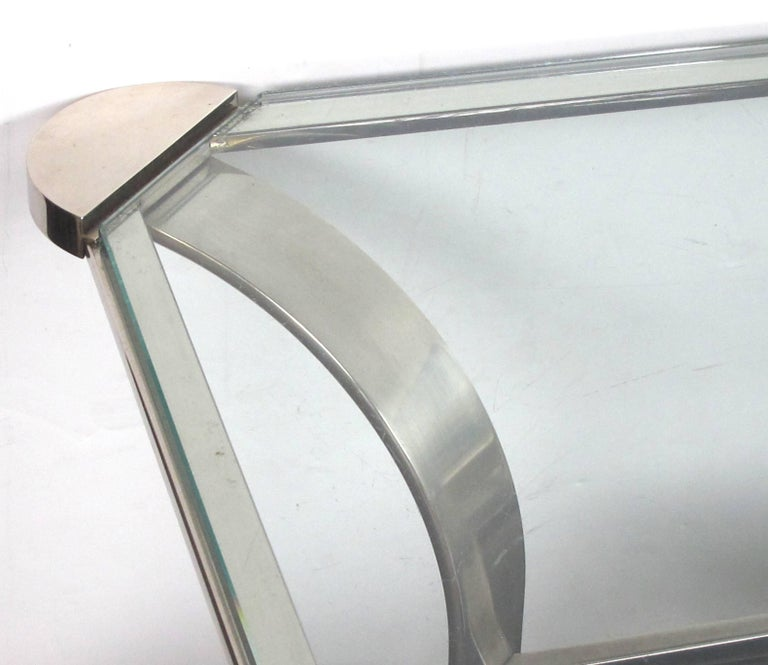 A stylish French 1970s steel rectangular-form coffee table with clear glass top and black glass lower shelf; the inset rectangular glass top with exaggerated rounded corners; raised on dramatic incurved steel supports joined by a lower shelf of
