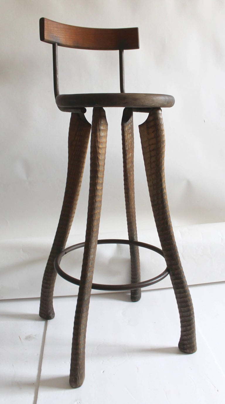 This folky handmade bar stool and all hand-carved legs. The iron footrest matches the iron rungs on the back of the seat attached. Take special notice to the details in the hand-carved legs. The condition is very good and comfortable.