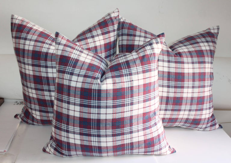 This collection of three 19th century plaid cotton linen pillows have a natural linen backing. These muted colors are red, white and blue. Nice crisp white linen backings.