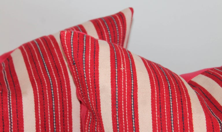 These interesting cotton red and white ticking pillows have red cotton linen backing. The inserts are down and feather fill. Two pairs in stock.