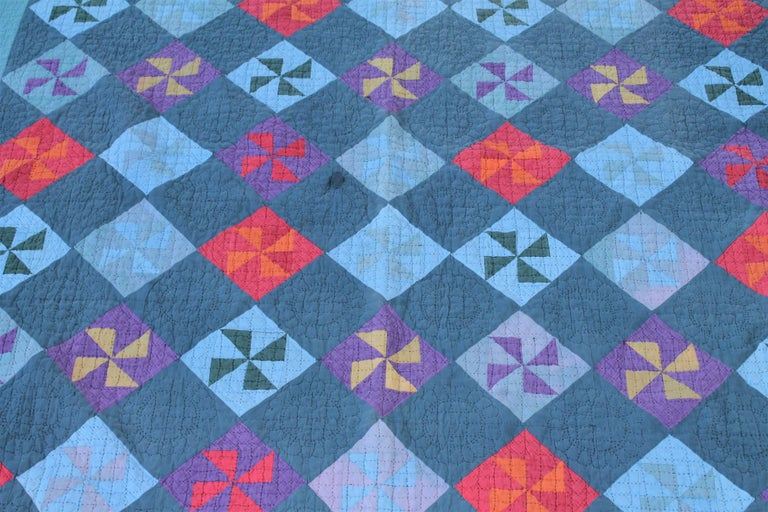 This mid-western Amish pin wheel quilt is in good condition with one minor circular repair. The piece work and quilting is in good condition. The quilt has overall muted colors. It has a triangular border.