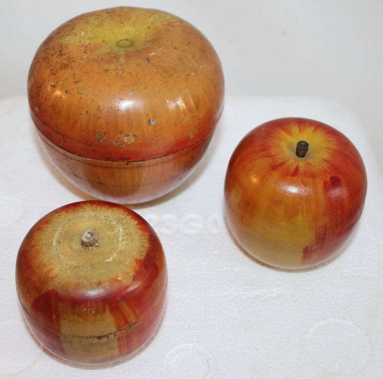 "The large tin painted apple is signed Wyandotte Toys is on the large tin candy container, the large tin apple is 4.5"" tall. The other two wood apples are hand painted and hand carved and marked: