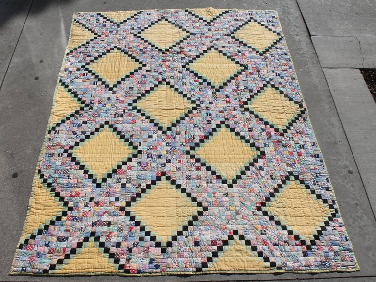 This tiny pieced postage stamp chain is in good condition. The yellow and green ground is a light nice shade. This quilt is comprised of floral feed sack fabrics.