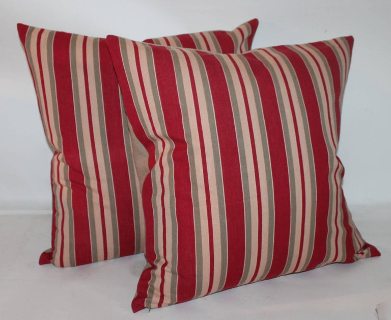 These tan and red striped ticking pillows are in fine condition. The backings are in a cream cotton linen. Four pairs in stock 20 x 20 / 22 x 22.