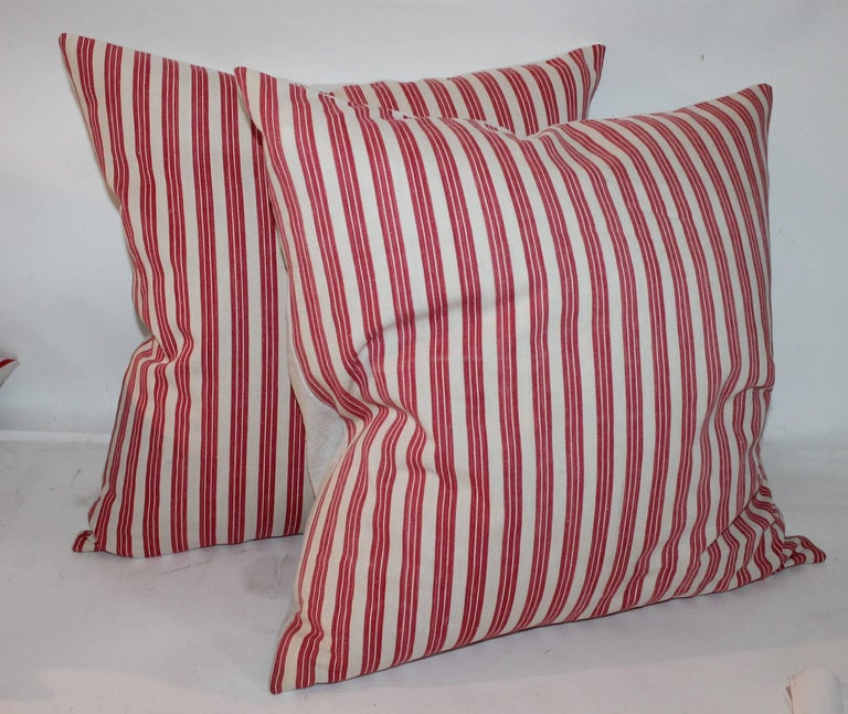 These red and white stripe ticking pillows are in fine condition. They come in sizes 20 x 20 and in 22 x 22. Four pairs in stock.