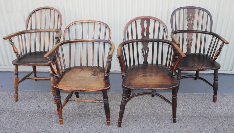 Collection of four Windsor chairs from England. All four chairs are slightly different. Fantastic patina and all in sturdy condition. Minor old small repairs here and there. Wear consistent from age and use.
