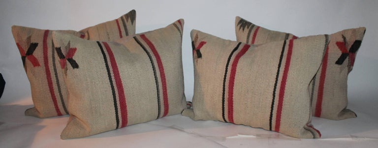 These early Navajo Indian weaving saddle blanket pillows are sold individually. They are all in fine condition and evenly faded throughout. The backing is in tan cotton linen. Sold @ 895.00 each or all four for $ 3200.00.