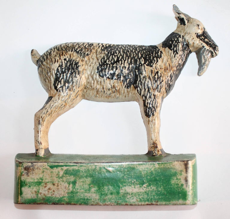 This early 20th century original painted cast iron goat is in good condition with wear consistent from age and use.