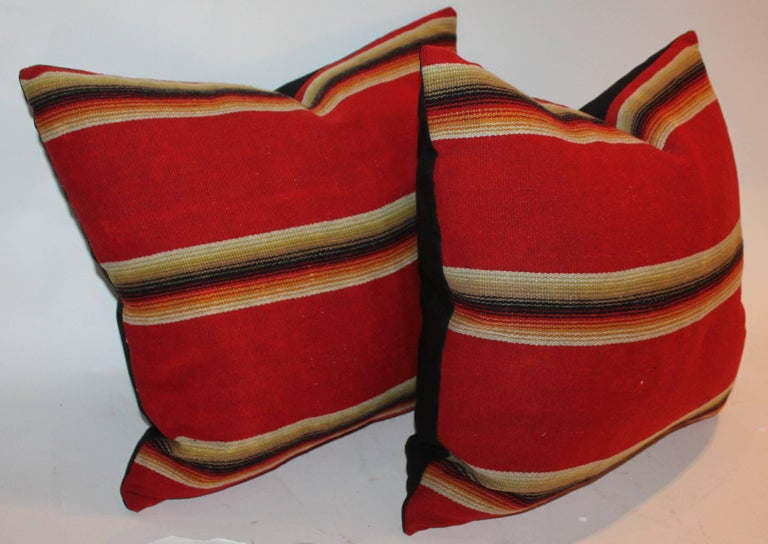Wool serape Indian sunset pillows in fine condition. The backing is in black cotton linen. Sold as a matching pair.