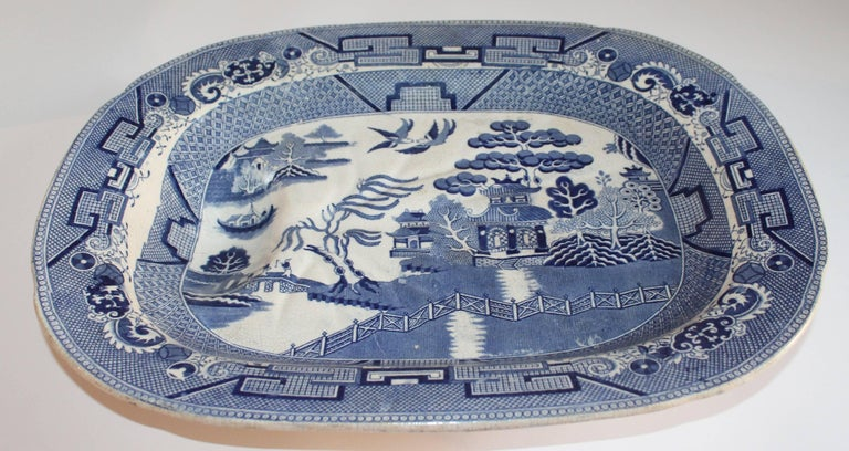 Early 19th century English Blue Willow Meat platter with the drain built in the base. This large tray is unsigned and is footed. The condition is very good with crazing and age spots on the reverse.
