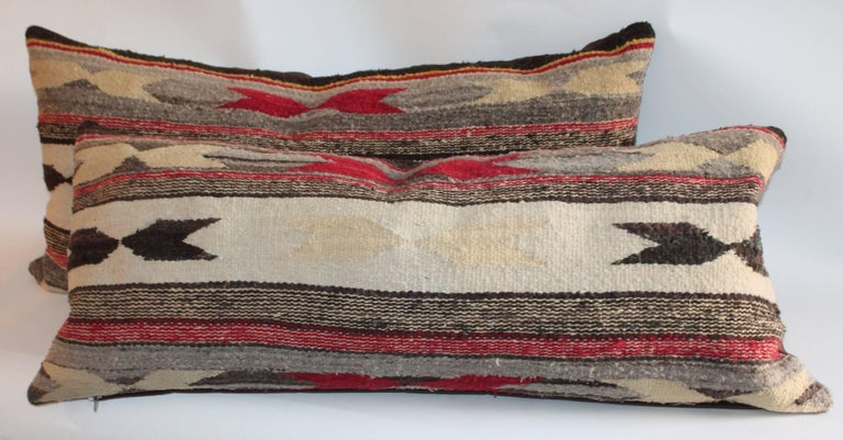 These Navajo Indian weaving bolster pillows have three color and chevron pattern. The backing is in a brown cotton linen.