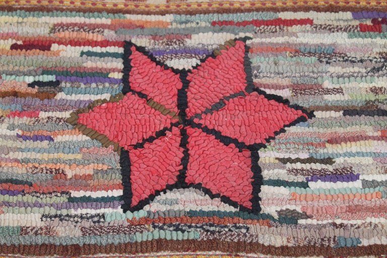 This amazing little gem is very early example of a sampler or child's hand hooked rug mounted on stretcher frame. The entire rug including the fringe is hand woven in very early country colors. It is all hand-sewn on cotton linen.