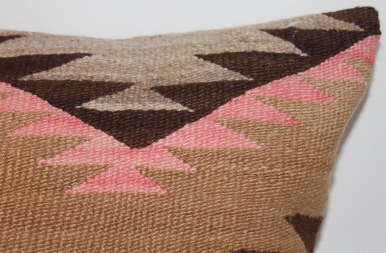 Navajo Indian weaving bolster pillow is in muted mauve, tan and brown colors with a light brown backing. The condition is very good. This is a large bolster pillow in comparison with the others.