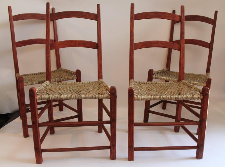These folky red painted ladder back chairs from Canada are in good sturdy condition and they retain the original white painted rawhide seats. Seat height is 15 inches. They have a bittersweet/redish surface. Set of four are all in good condition.