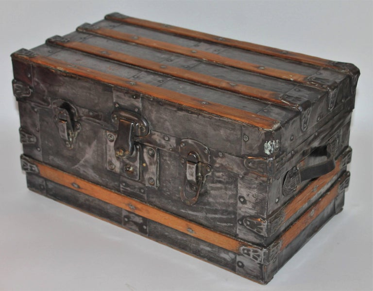 This 19th century small trunk would be great for a doll or teddy bear collection. It has a Industrial look with natural tin over wood and wood slated sides and top. It is signed Eagle Lock Co. USA / Terryville,Conn. on the metal closures. The