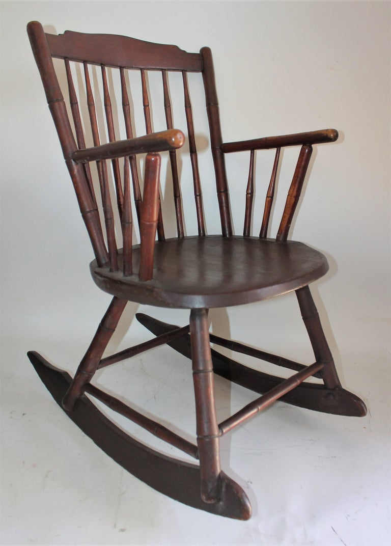 19th century windsor rocking chair in fine condition. This is a very sturdy rocking chair. Minor little old repairs. It has a wide seat and back. This rocking chair has a wonderful aged patina.