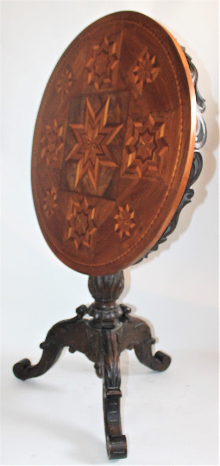This 19th century hand-carved table with inlaid lift top has hand inlaid stars in fine condition. This fancy table is made in Switzerland and is a real collectors dream. Looks great with Folk Art or Americana collection.