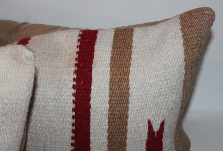 These Navajo Indian weaving saddle blanket bolster pillows are in good condition and have matching tan cotton linen backings. The inserts are down and feather fill.