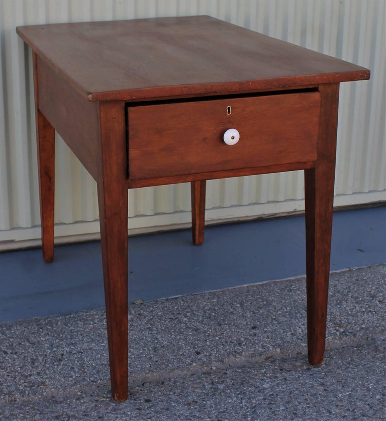 19th century original red painted work or side table. This large drawer has the original porcelain pull and dovetailed construction. This early kitchen work table makes a great side table in a living room. This painted pine table is from New