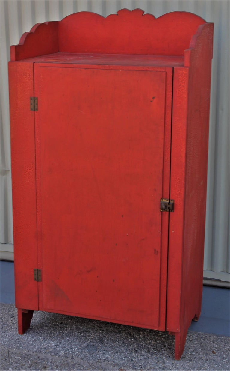 This 19th century red / orange one door wall cupboard has one door and many shelf's inside. Fancy cut-out and nice details. This is in very good condition with a wonderful alligatored painted surface.