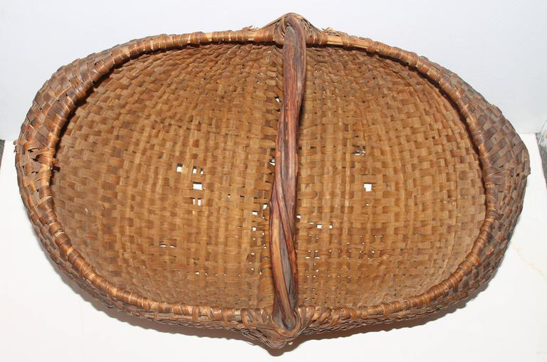 This very large all original basket is in fine as found condition with very minor breaks on the bottom. The handle is like a group of grapevines or twigs twisted together as one. This basket is quite unusual and a great addition to any basket or