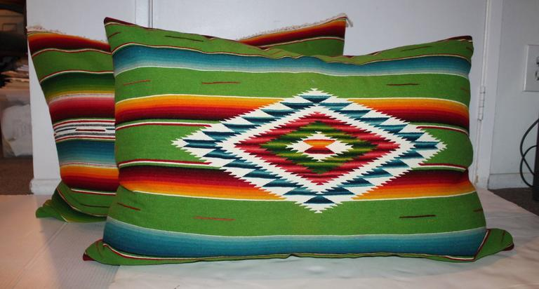 These vibrant large bolster pillows are amazing and one has the center motif and one in back is all stripes. The backings are in red cotton linen. Sold as a pair.