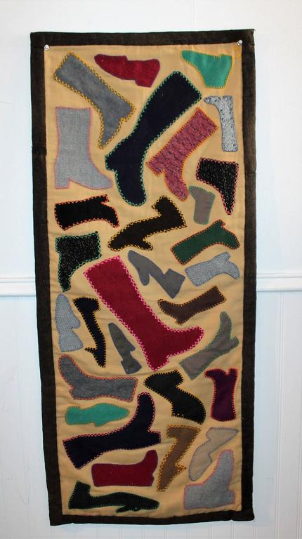 This folky pictorial handmade wool boot and shoe applique runner has the original blue ticking backing. This wonderful Folk Art textile has a velcro backing trim for hanging on a wall or framed stretcher. The binding edge is made from an old wool