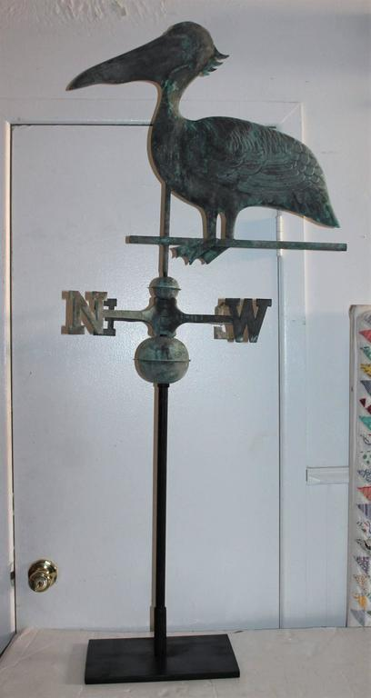 This fun crazy shore bird has a wonderful aged surface and its original patinated directionals. This great weather vane has the original iron rod of which could be mounted on a roof top or kept on the custom iron base. This is included. Condition is