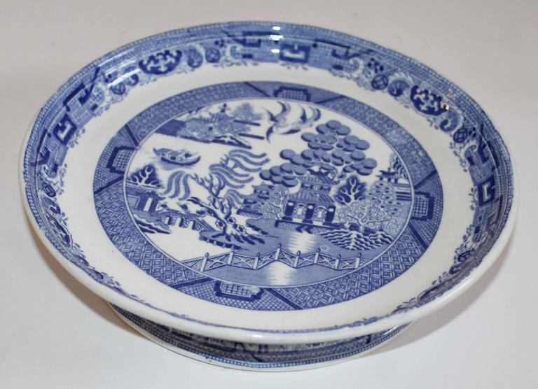 19th century blue willow cake platter. This great blue willow cake platter is in amazing condition. The stand is white and features the classic Blue Willow pattern. The pedestal of the stand also features blue detailing around the base.