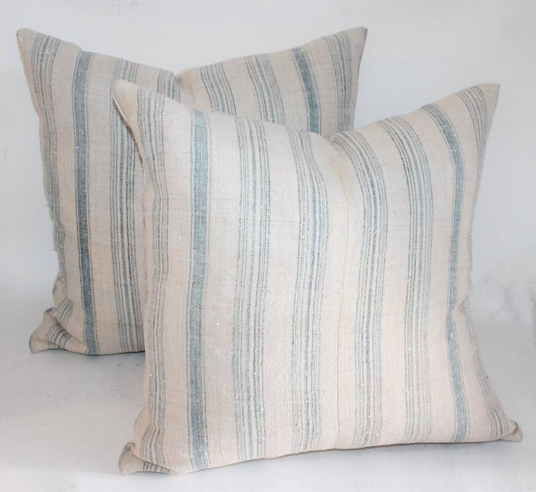We have two vintage pairs of light blue and white ticking pillows in great condition. This set of four pillows are professionally laundered and have been fitted with down and feather inserts. All pillows are made in house. Sold as a group of four.