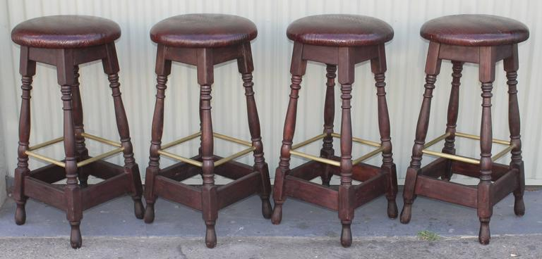 This set of four matching bar stools are in leather top seats and a turned leg base. The foot rests are in brass and are surround on all four sides. The newly done seats are in a reptile embossed texture. Fantastic condition and very comfortable.